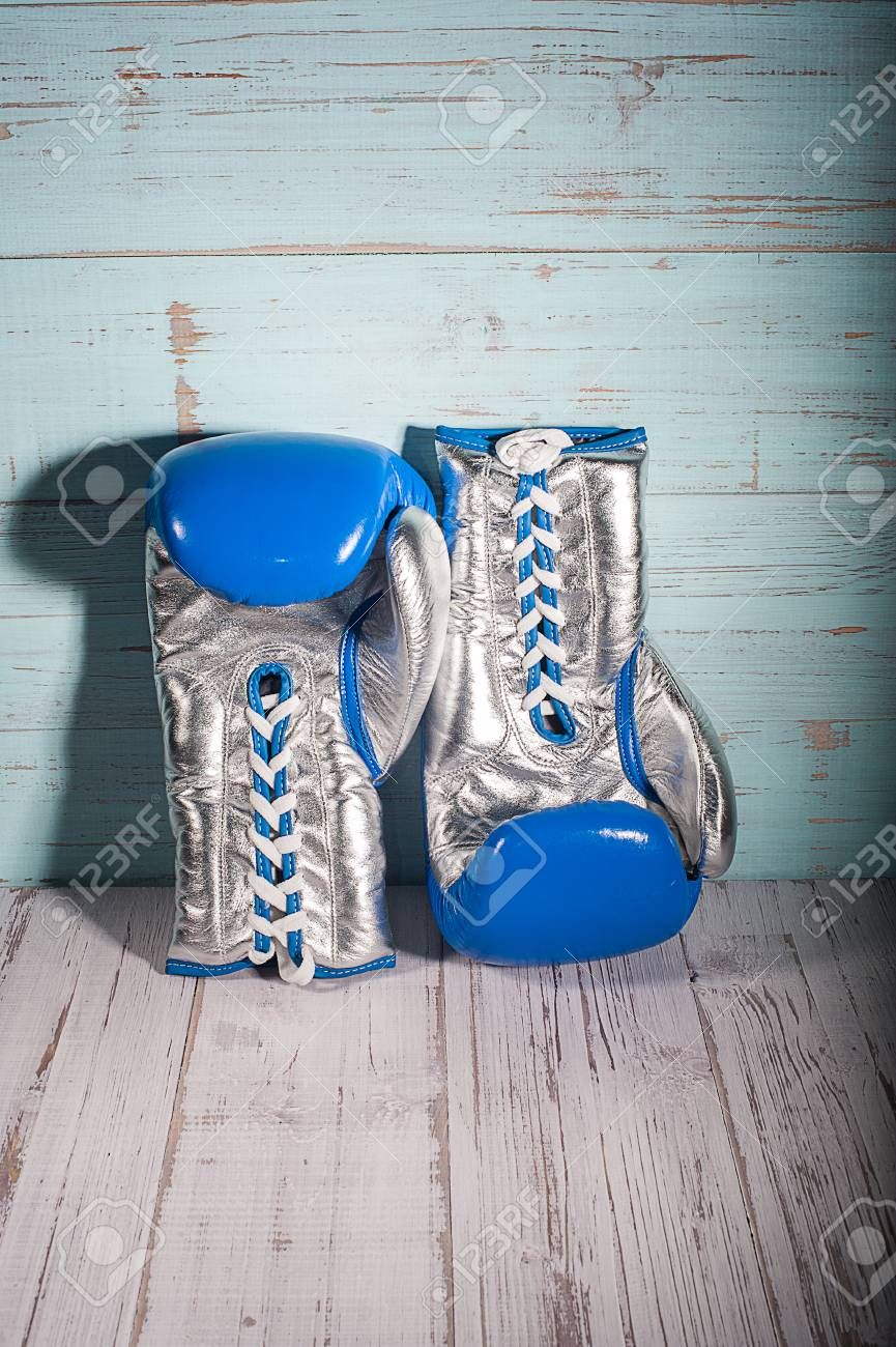 Silver and blue boxing gloves on blue and white cracked wooden