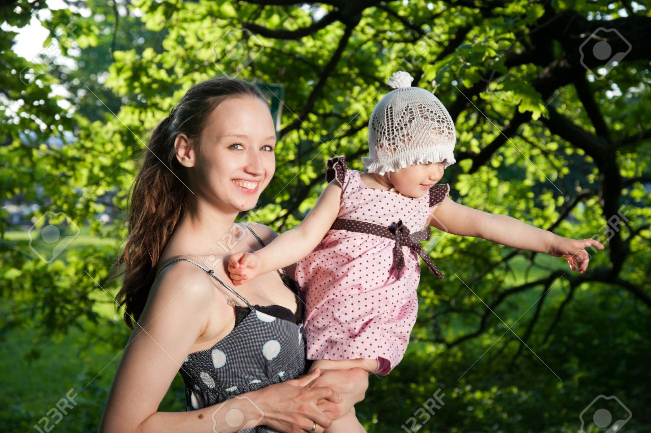 Woman holds child on the background of trees Stock Photo - 13725627