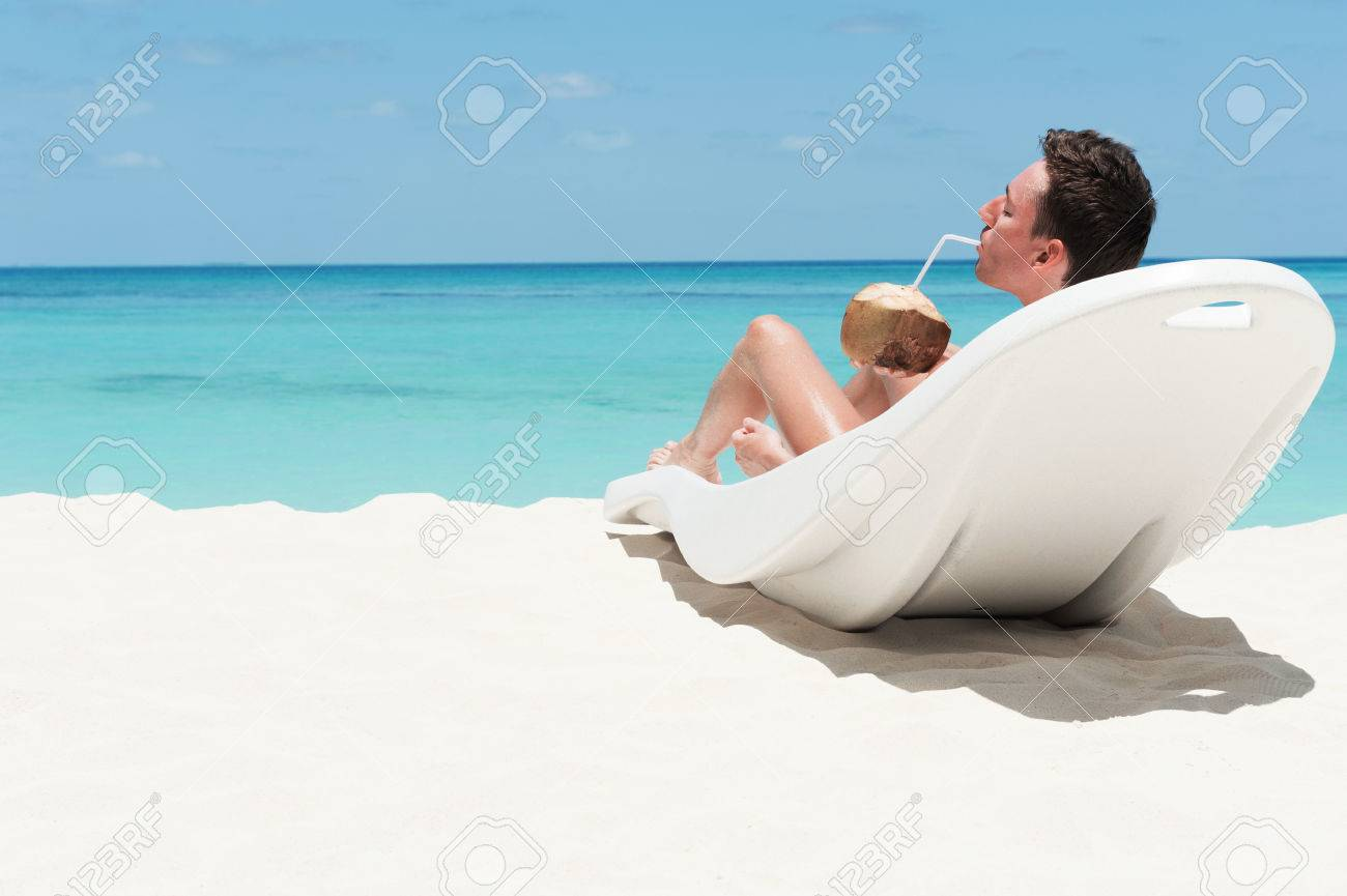Man Enjoy Lying On Lounger Sunbed And Drinking Coconut Cocktail Beach With White Sand