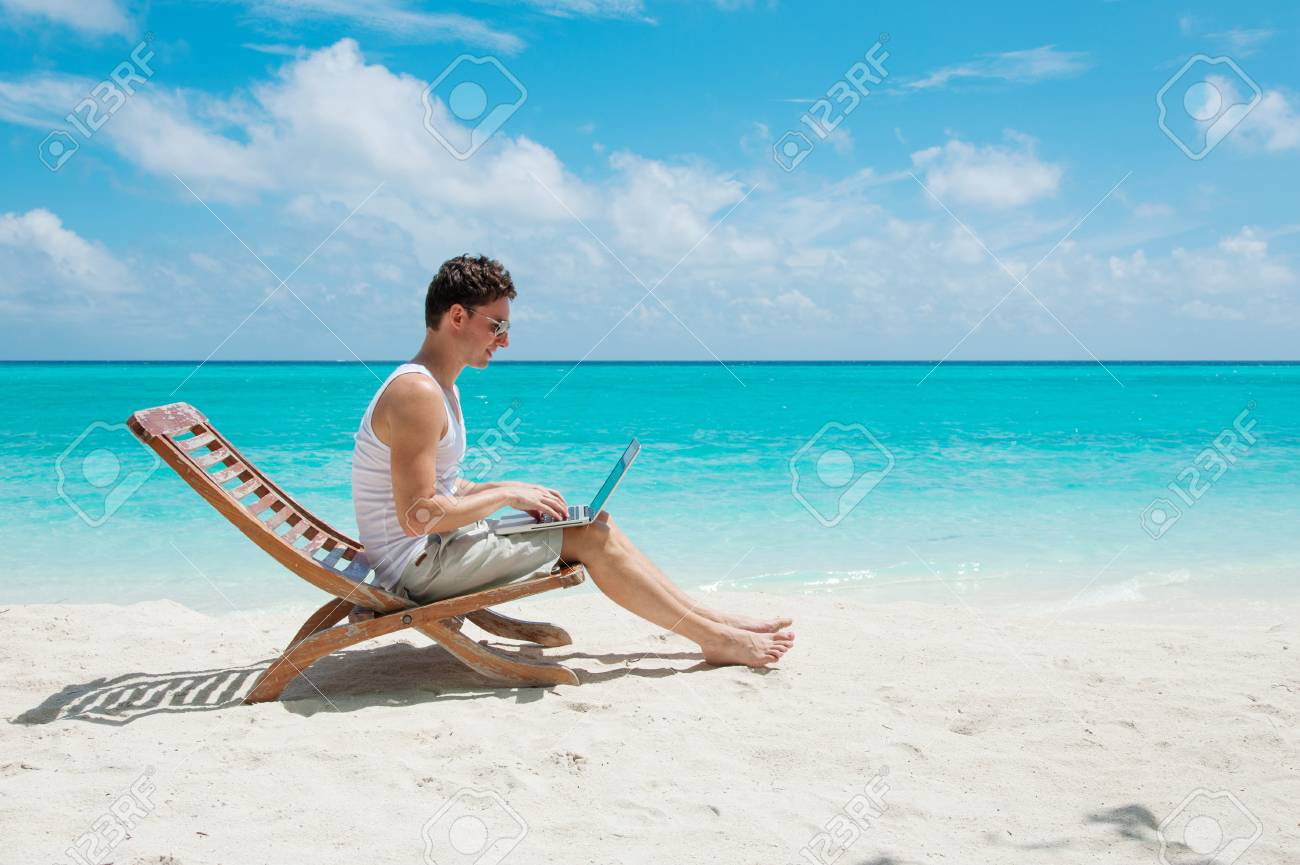 man relaxing at the beach with laptop maldives island ocean