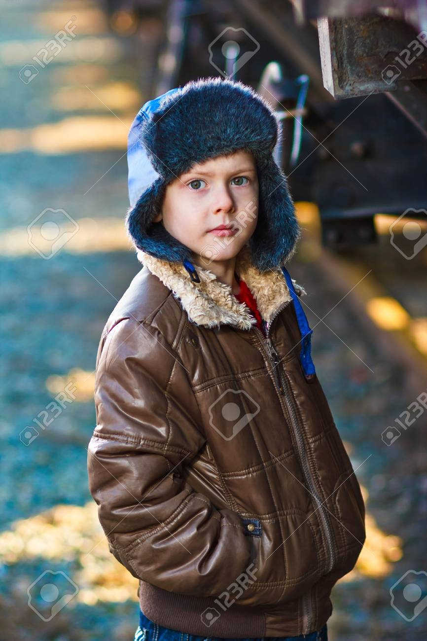 Boy homeless bum on street freezing close to railway carriage hat and jacket Stock Photo - 16923255