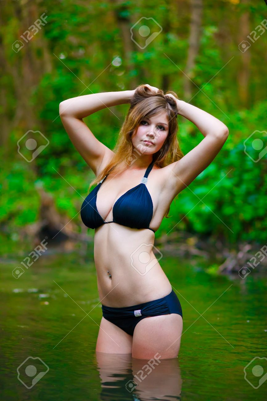 Blonde young woman with big breasts in a black bikini standing..