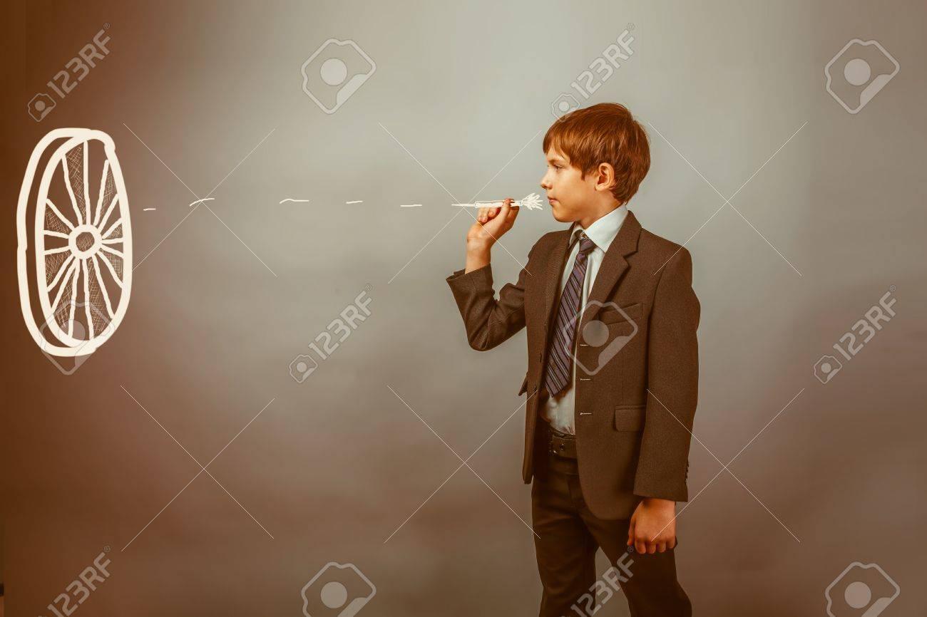 Teen boy businessman throwing darts at a target dart on a blue