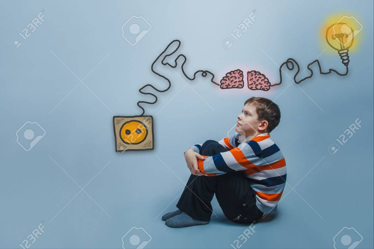 Boy sitting on the floor hugging his arms legs and looking up charging cord plug wire