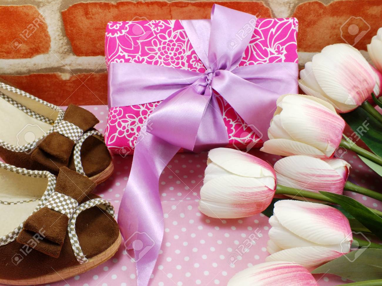 pink gift box and ladies shoes on pink polka dot background