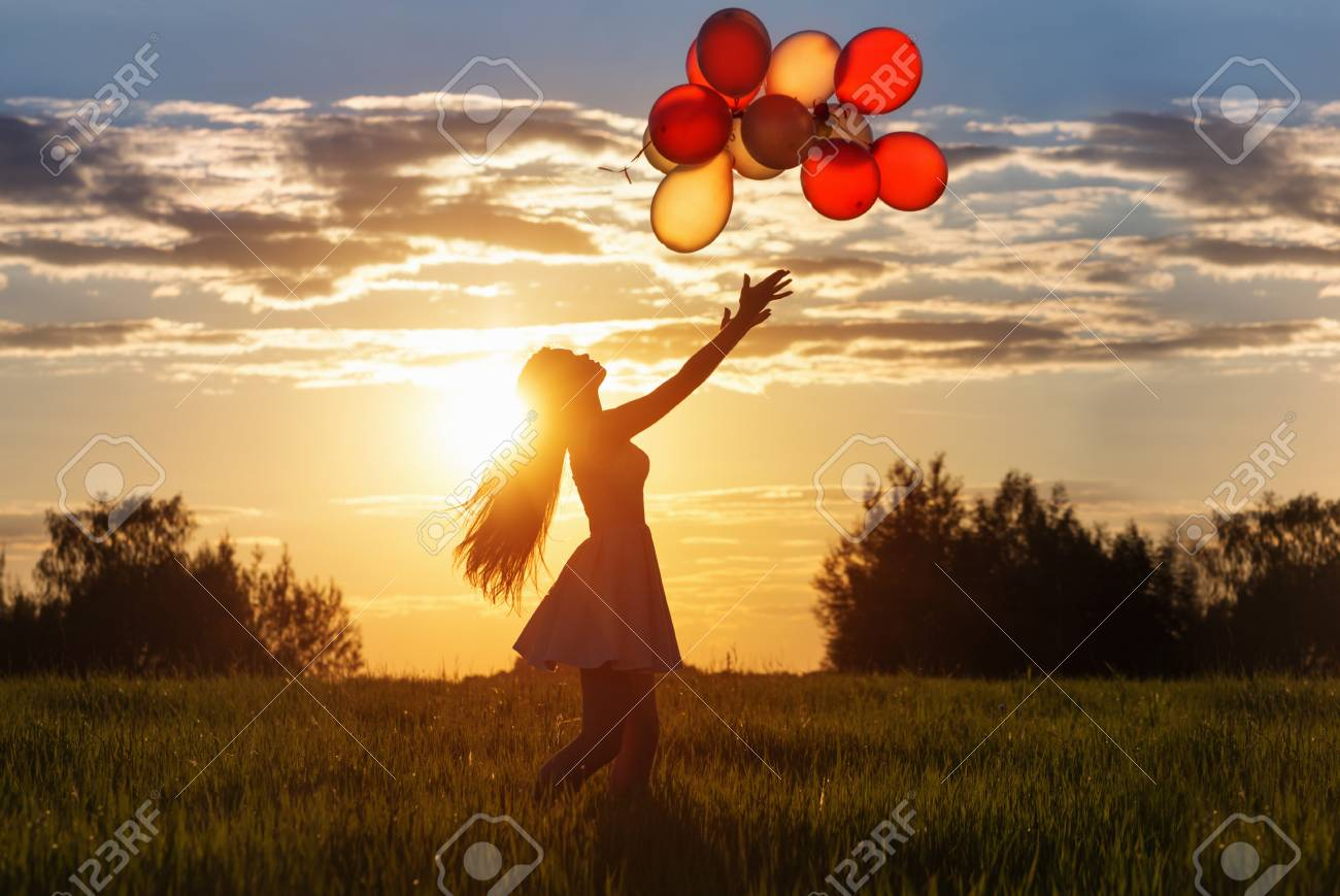 Girl with balloons at sunset stock photo 90854231