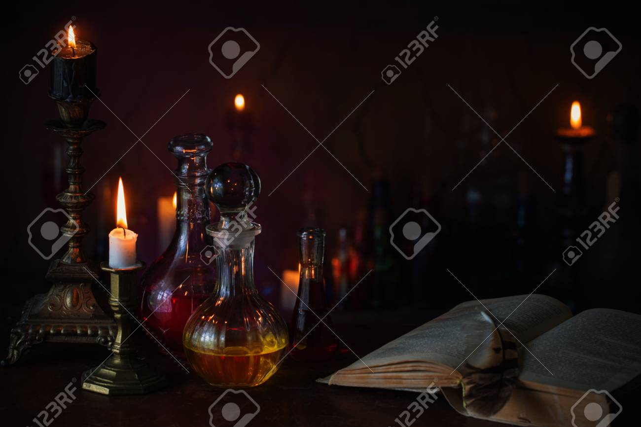 Magic potion, ancient books and candles on dark background - 94217531