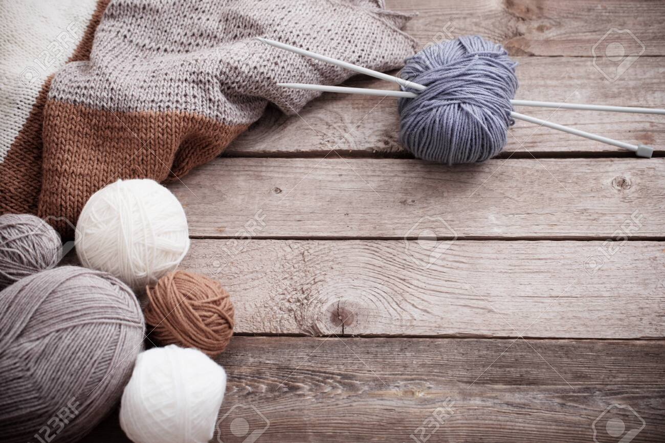 Knitting and knitting needles on a wooden surface - 124556041