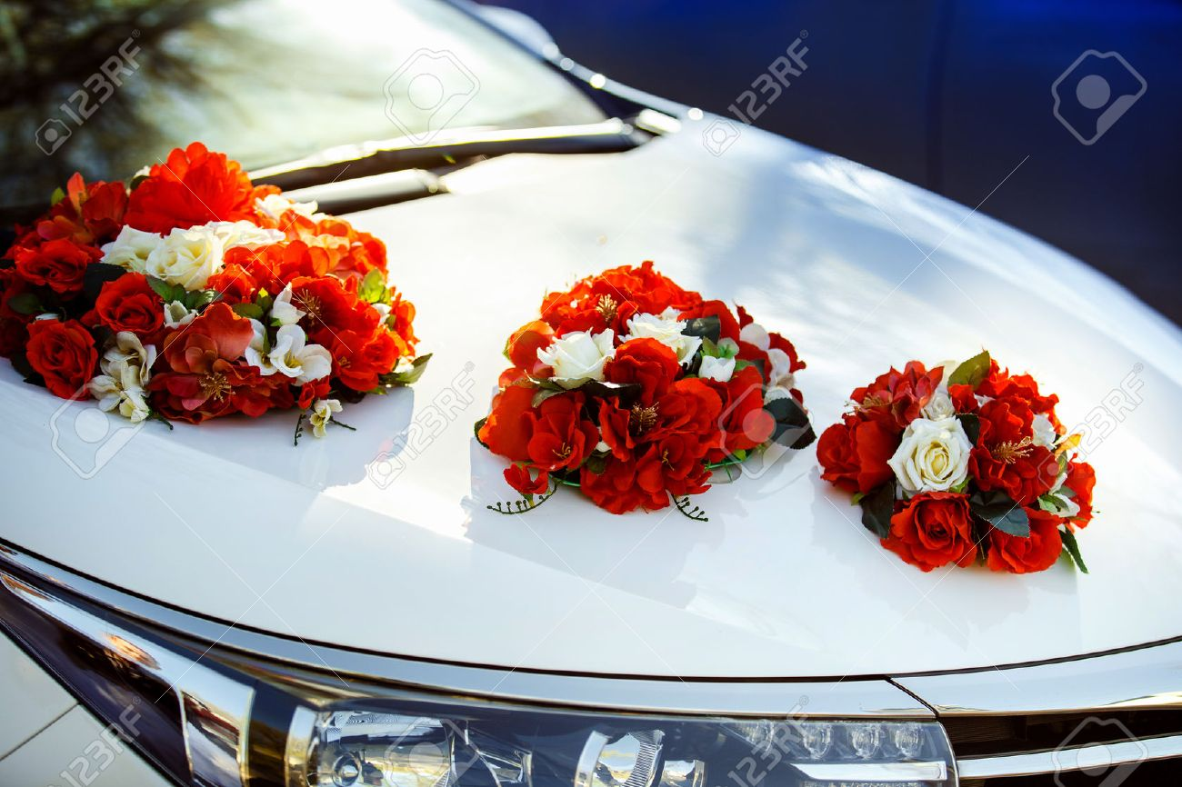 Closeup image of wedding car decoration with red and white flowers..