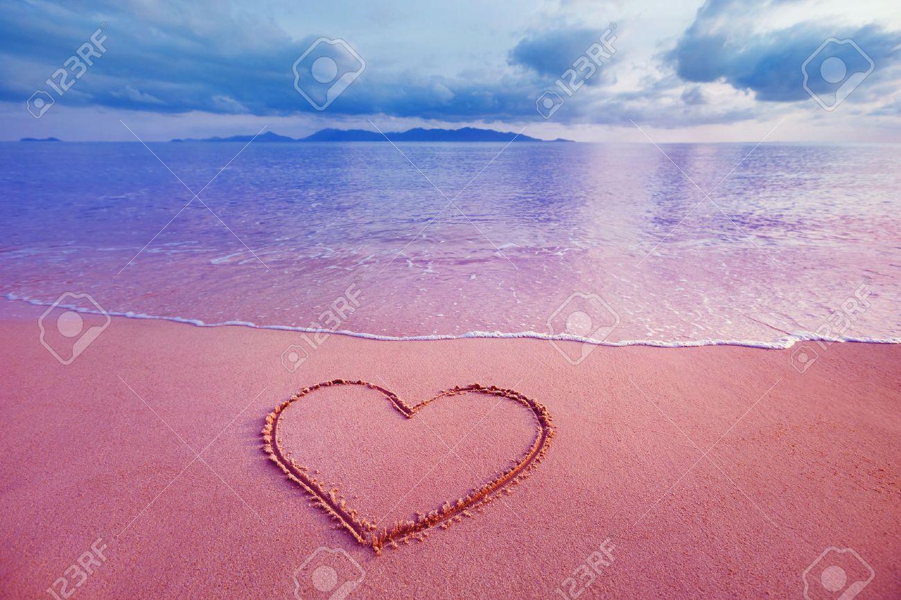 Closeup image of heart symbol written on sand at pink sea sunrise background. - 53750559