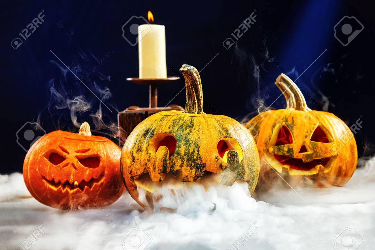 Halloween Wallpaper With Three Jack O Lantern Pumpkins Surrounded
