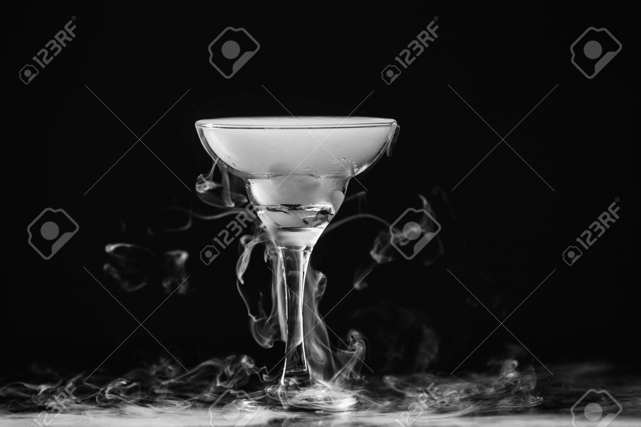 Closeup wine glass with white fog at dark background chemical reaction of dry ice with