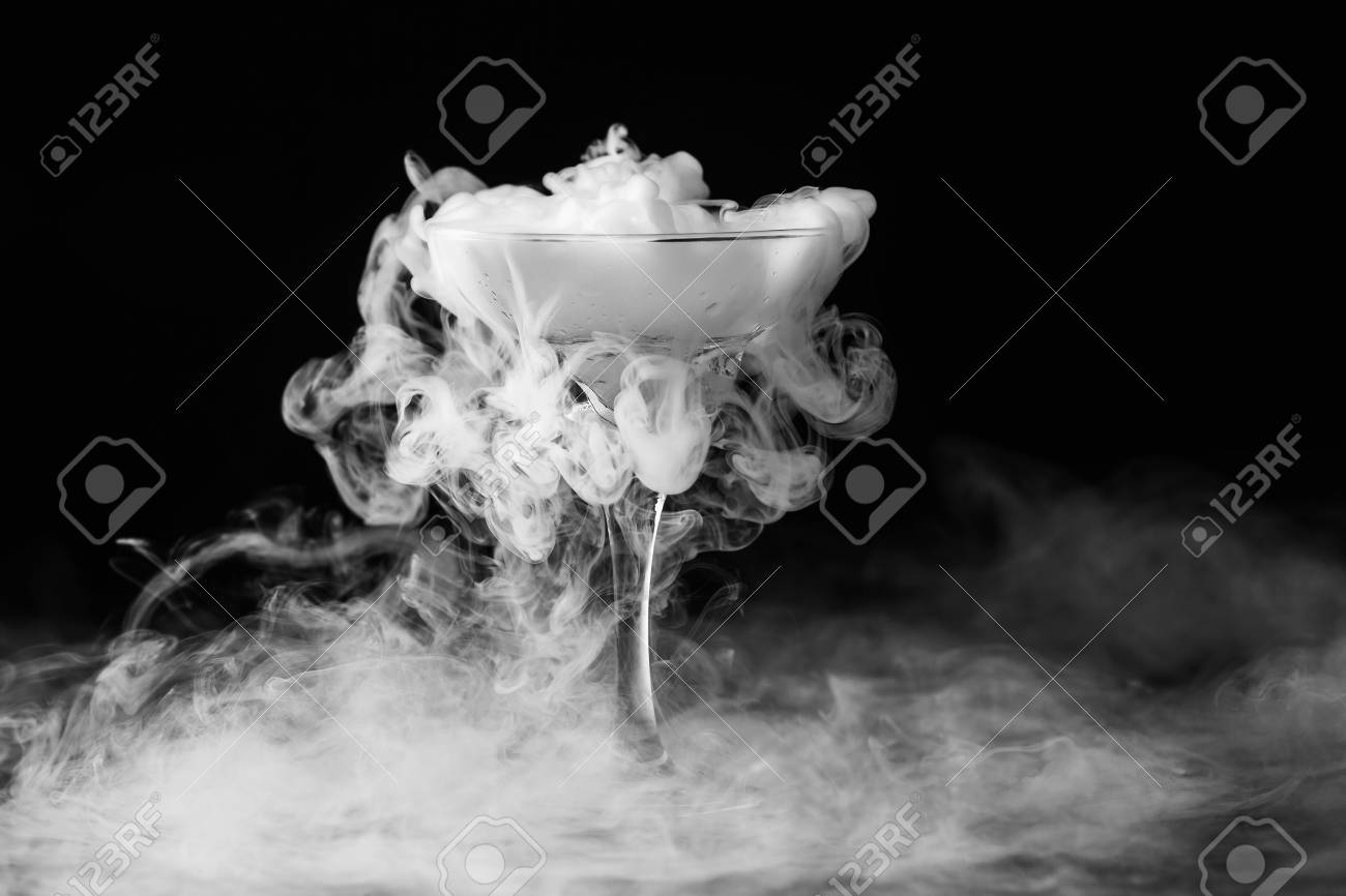 Closeup glass with white fog at dark background chemical reaction of dry ice with water