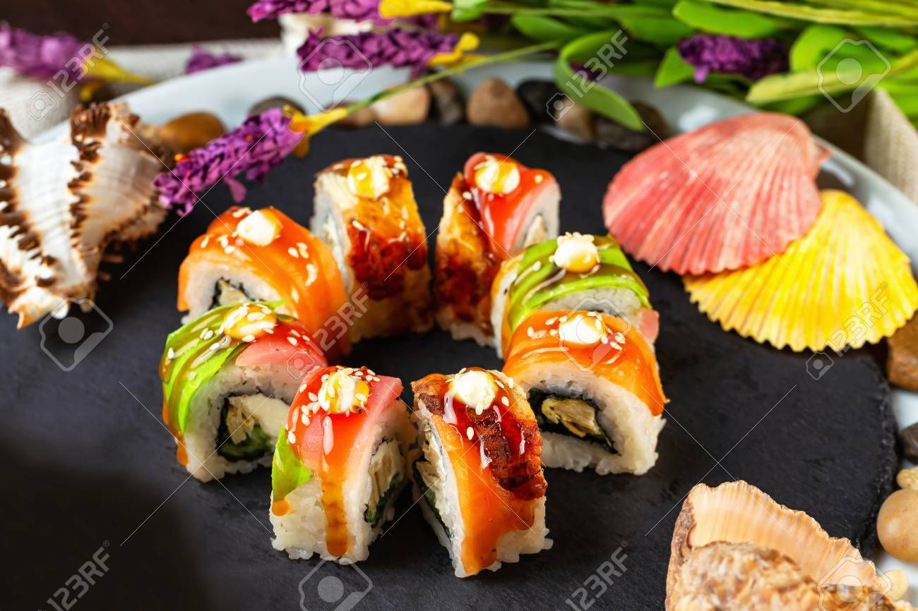 Rainbow Sushi Rolls Decorated With Teriyaki Sauce At Stone Tray