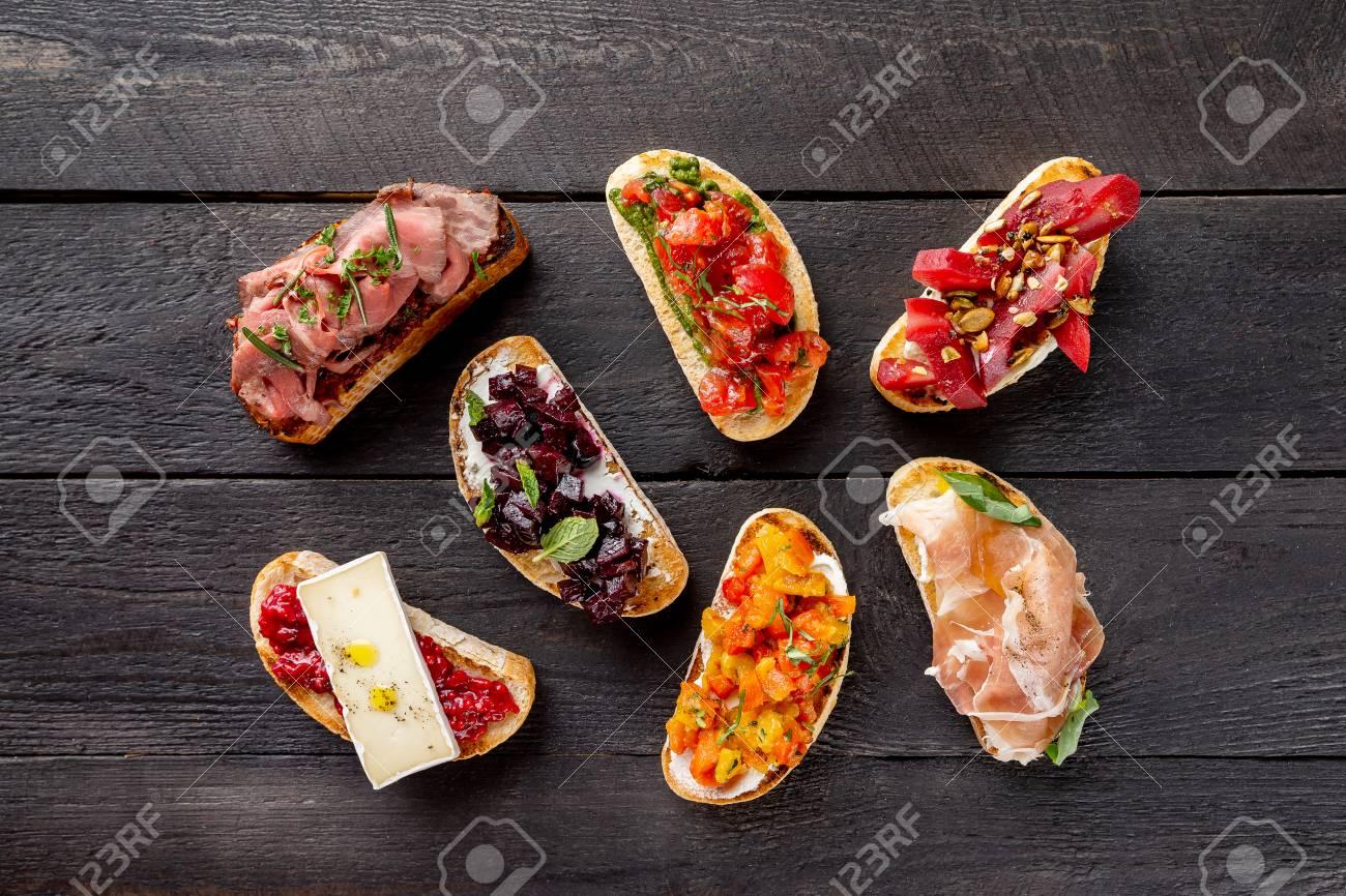 Top view italian bruschettas set at wooden board background. - 125219412