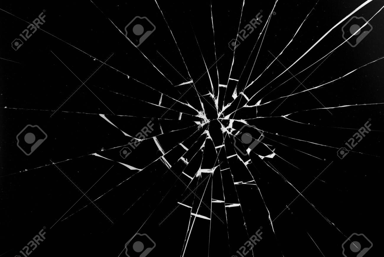 Round white cracks in glass on black background. - 139690842