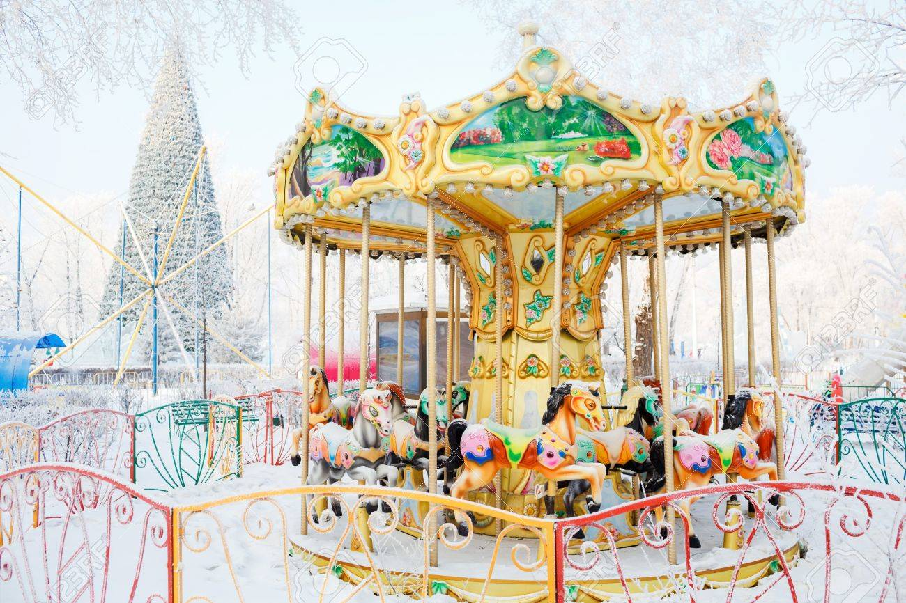Merry Go Round With Traditional Horses Covered Snow Behind The Carousel