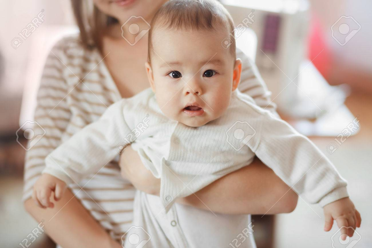 Stock photo the cute little baby boy in the arms of mom on the air mother and infant infant care children and kids growing