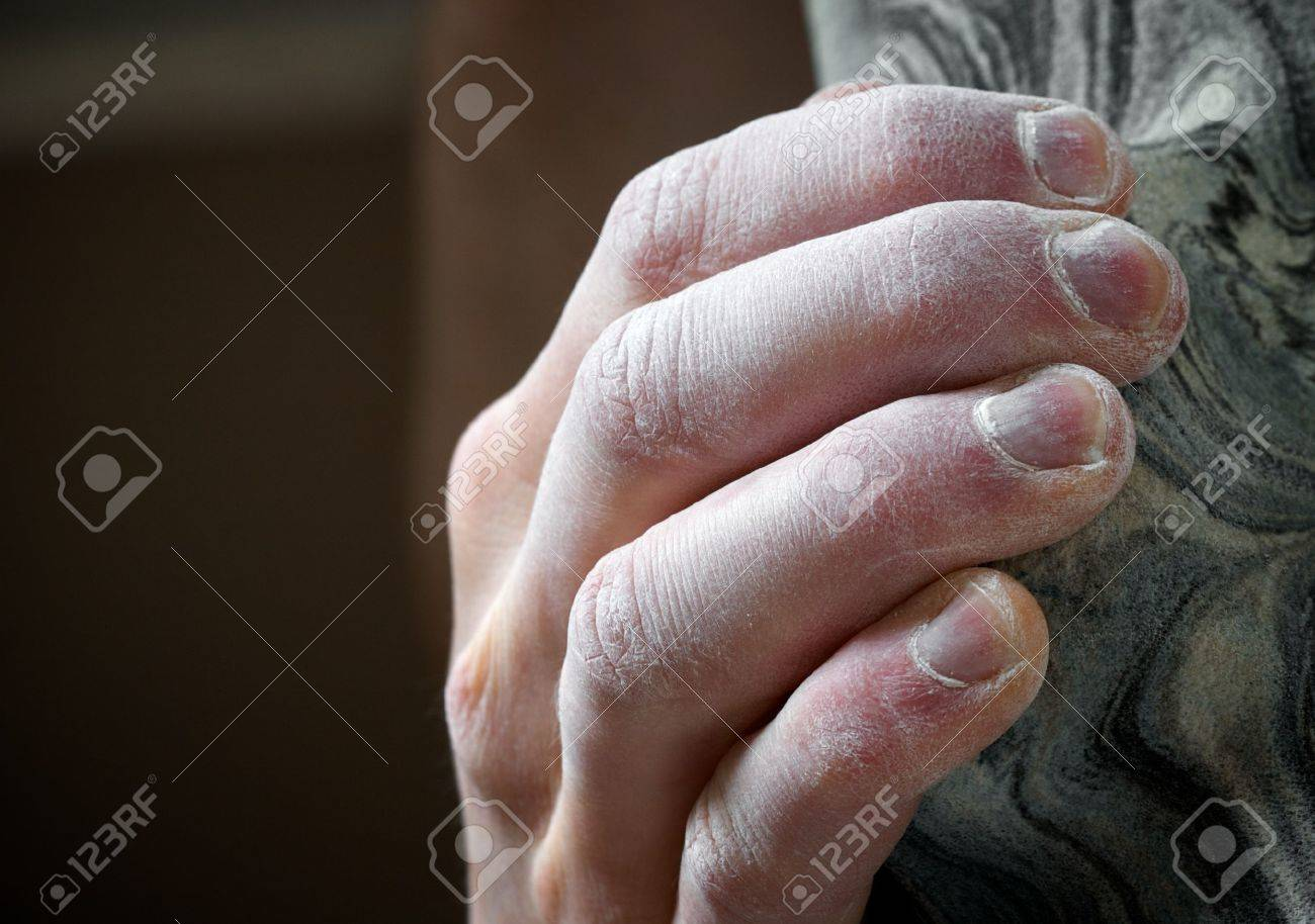 Chalked hand grips tightly to hang off an artifical climbing hold. Shallow depth of field Stock Photo - 4971564