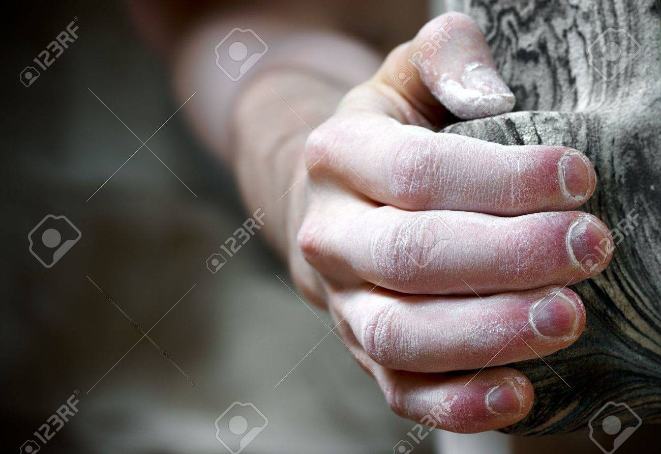 Chalked hand grips tightly to hang off an artifical climbing hold. Shallow depth of field Stock Photo - 4971561