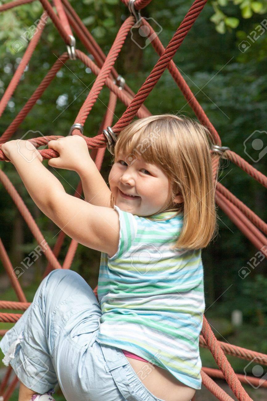 Kleine Blonde Mädchen Klettern Ein Seil Klettergerüst Lizenzfreie ...