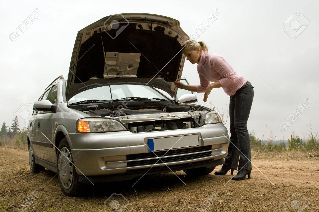 Young woman in a forest road with broken silver car. Stock Photo - 4856375