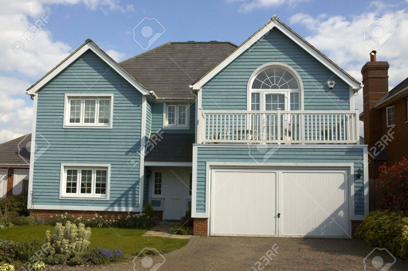 A blue wooden clad house with a cloudy sky Stock Photo - 3077452