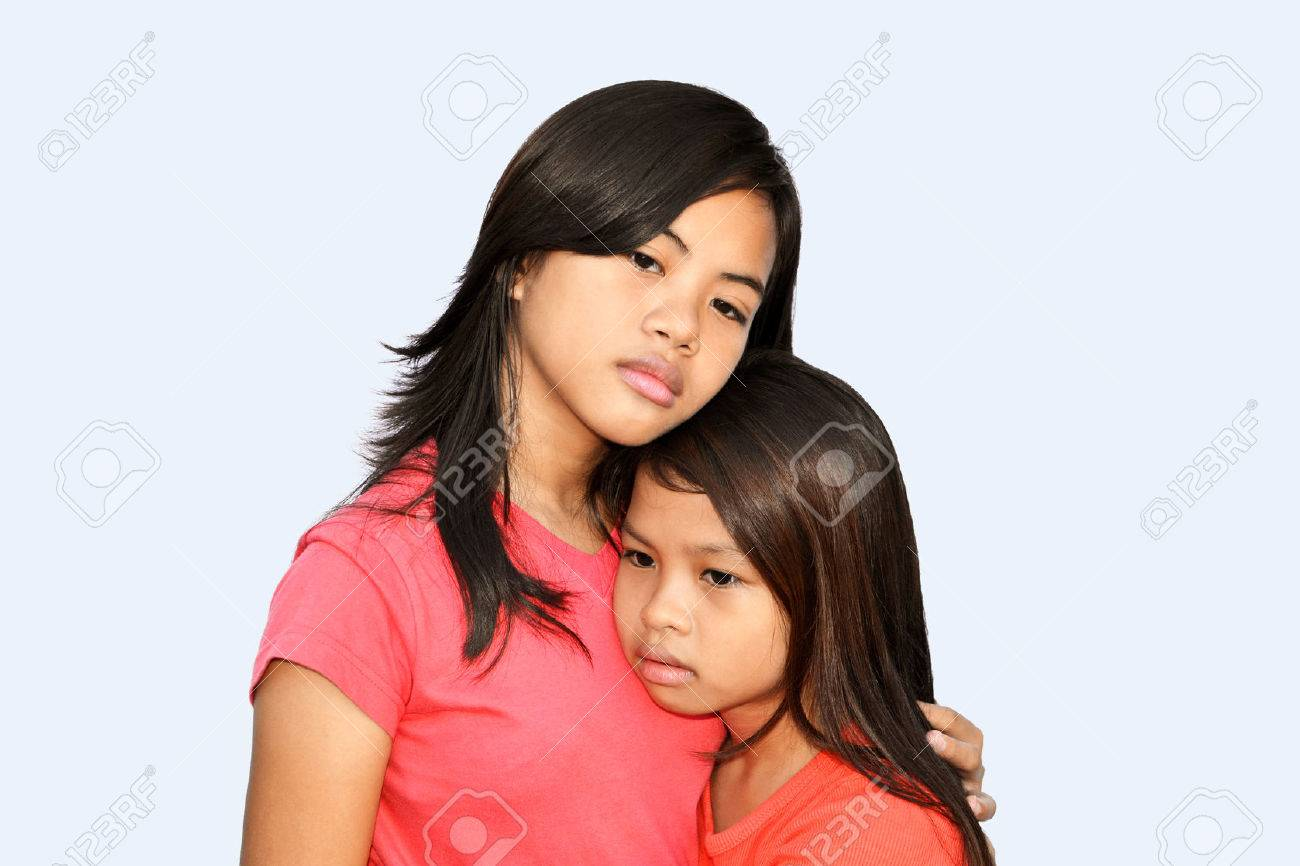 A teenager girl trying to comfort her younger sister with a hug & sad eyes! Stock Photo - 24890087