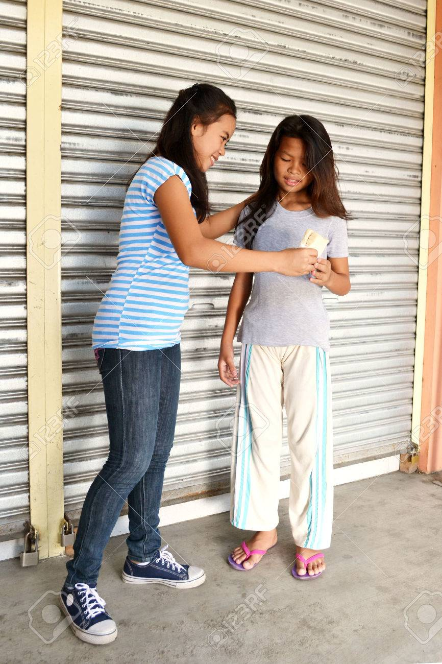 Young Asian lady helps poor little girl in the street by giving her a sandwich Stock Photo - 33396893