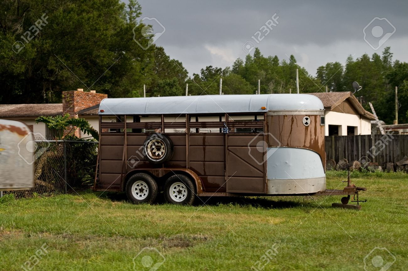 Old Brown Horse Trailer Parked On The Grass At A Small Ranch Stock Photo