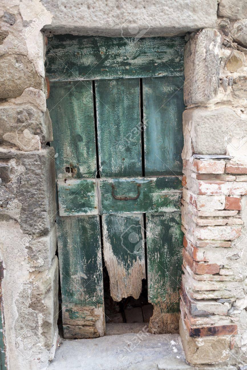 Vieille Porte En Bois Ancienne vieille porte en bois ragged dans un mur de pierre. italie lac de garde.  entrée dans une maison ancienne dans le village.