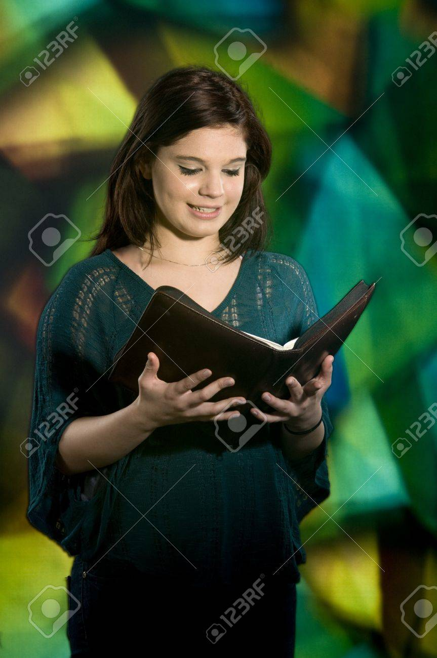 A young teen smiling as she reads her Bible in front of a large stained glass window Stock Photo - 13569391
