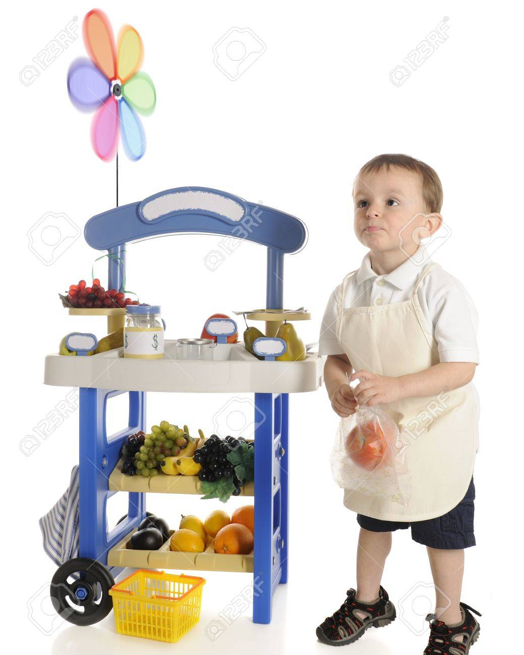 An adorable preschool fruit  vendor  standing by his fruit stand with an apple in a plastic bag, looking out towards customers  not visible    Motion blur on the pinwheel,  The stand Stock Photo - 13900106