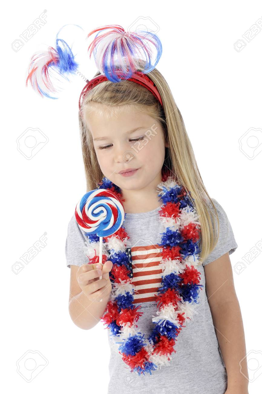 An adorable preschooler dressed to celebrate Independence Day, looking longingly at the red, white and blue swirrled lollipop she holds   On a white background Stock Photo - 13963645