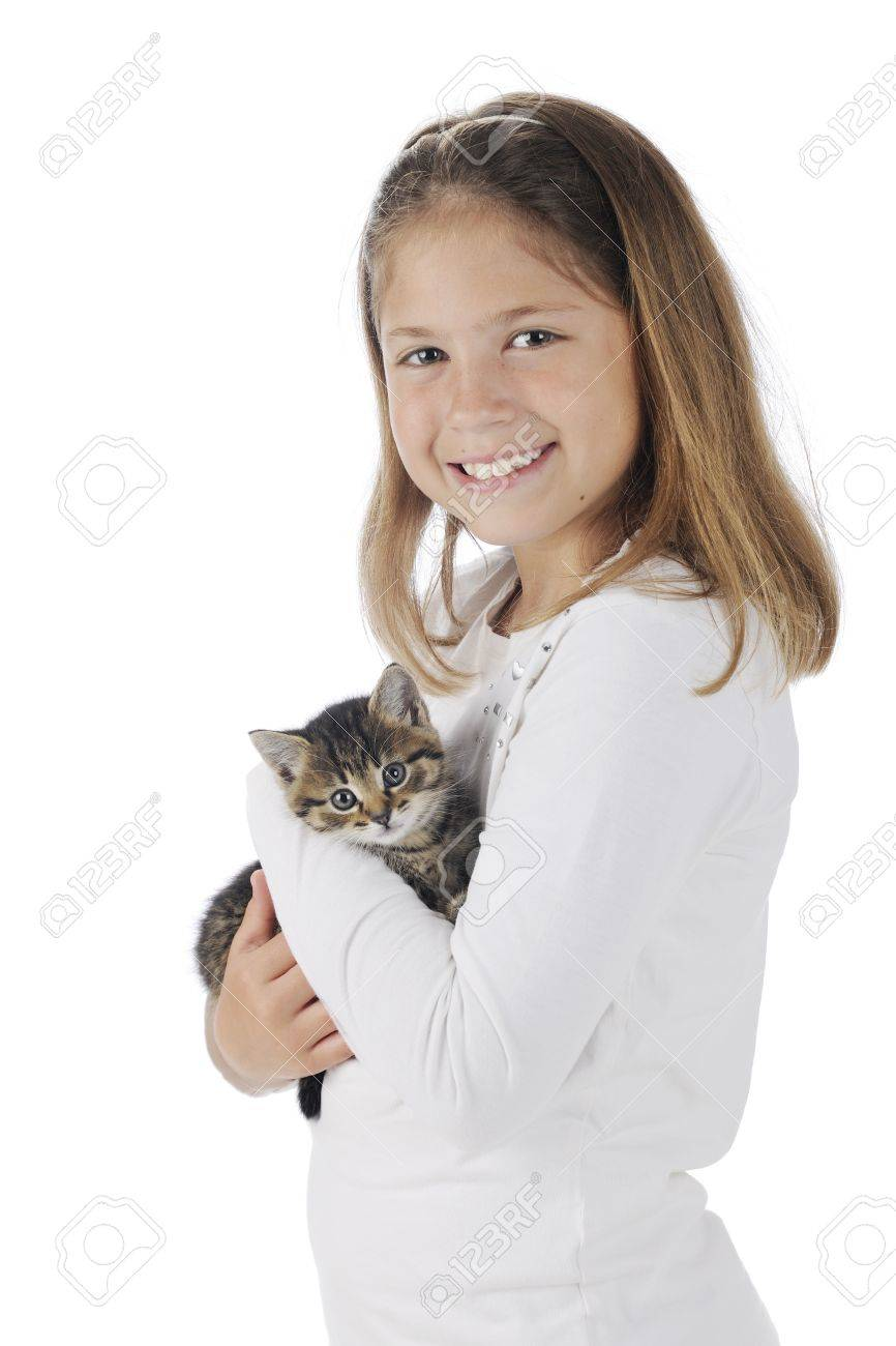 An attractive elementary girl proudly holding her pet kitten.  On a white background. Stock Photo - 14089814