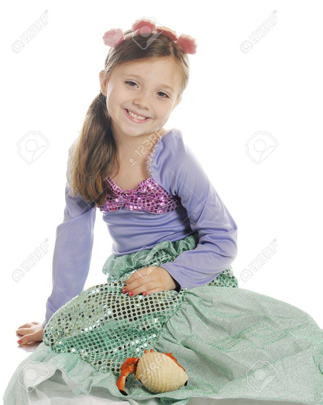 A beautiful elementary girl happily sitting with her pet hermit crab.  On a white background. Stock Photo - 14636350