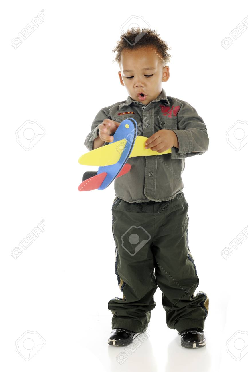 An adorable preschooler wearing an air force outfit impressed with the toy plane he holds   On a white background Stock Photo - 14668975