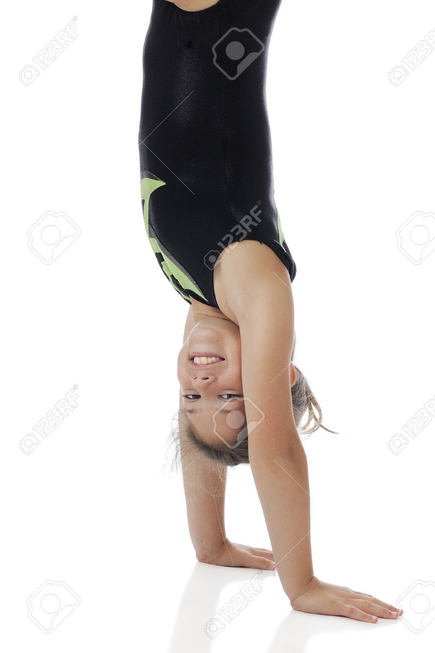 A happy elementary girl doing a handstand in her gymnastics leotards   On a white background Stock Photo - 14826478