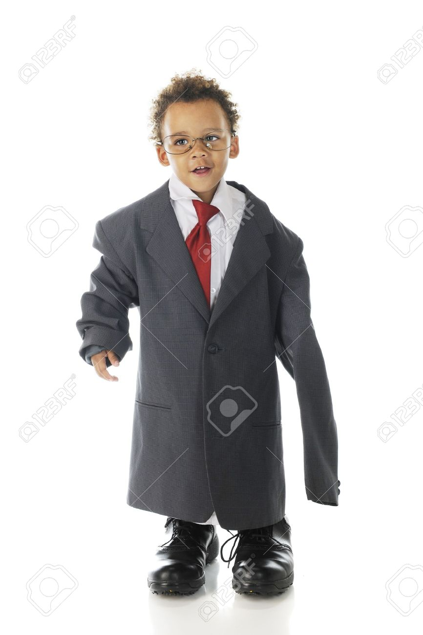 An adorable tot happily dressed in an oversized suit jacket, shirt and tie with his daddy's dress shoes.  On a white background. Stock Photo - 15003185