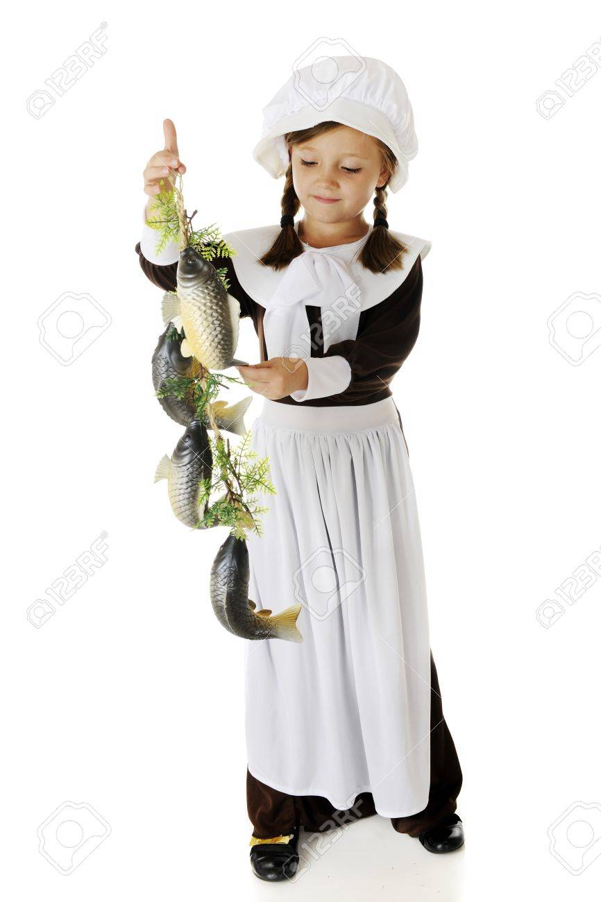 An attractive elementary Pilgrim girl admiring a string of fish, a likely food served at the first Thanksgiving    On a white background Stock Photo - 15041410