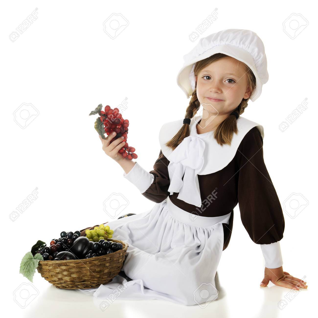 A pretty elementary Pilgrim girl happily sitting with a basket of fruit   On a white background Stock Photo - 15041411
