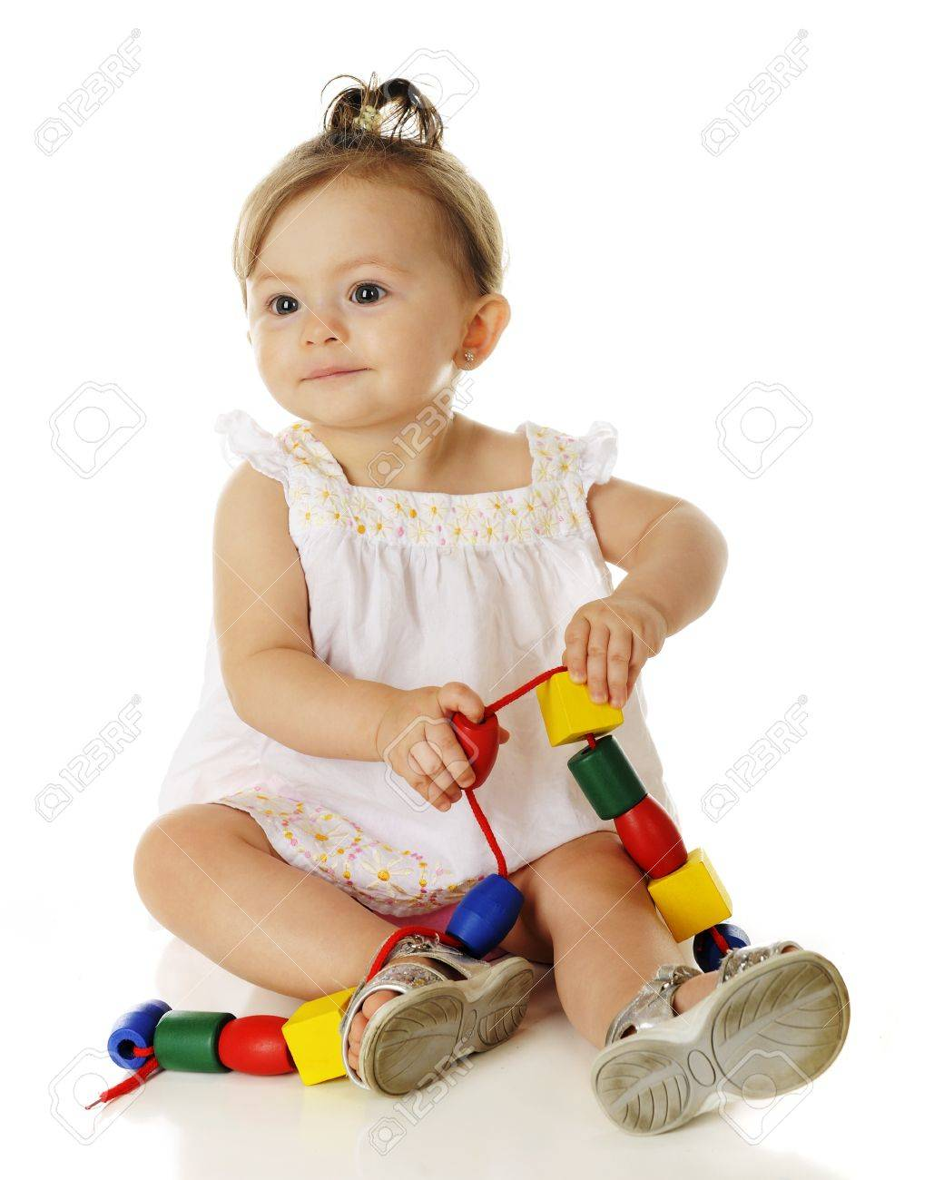 An Adorable Baby Girl Happily Playing With Large Wooden Beads