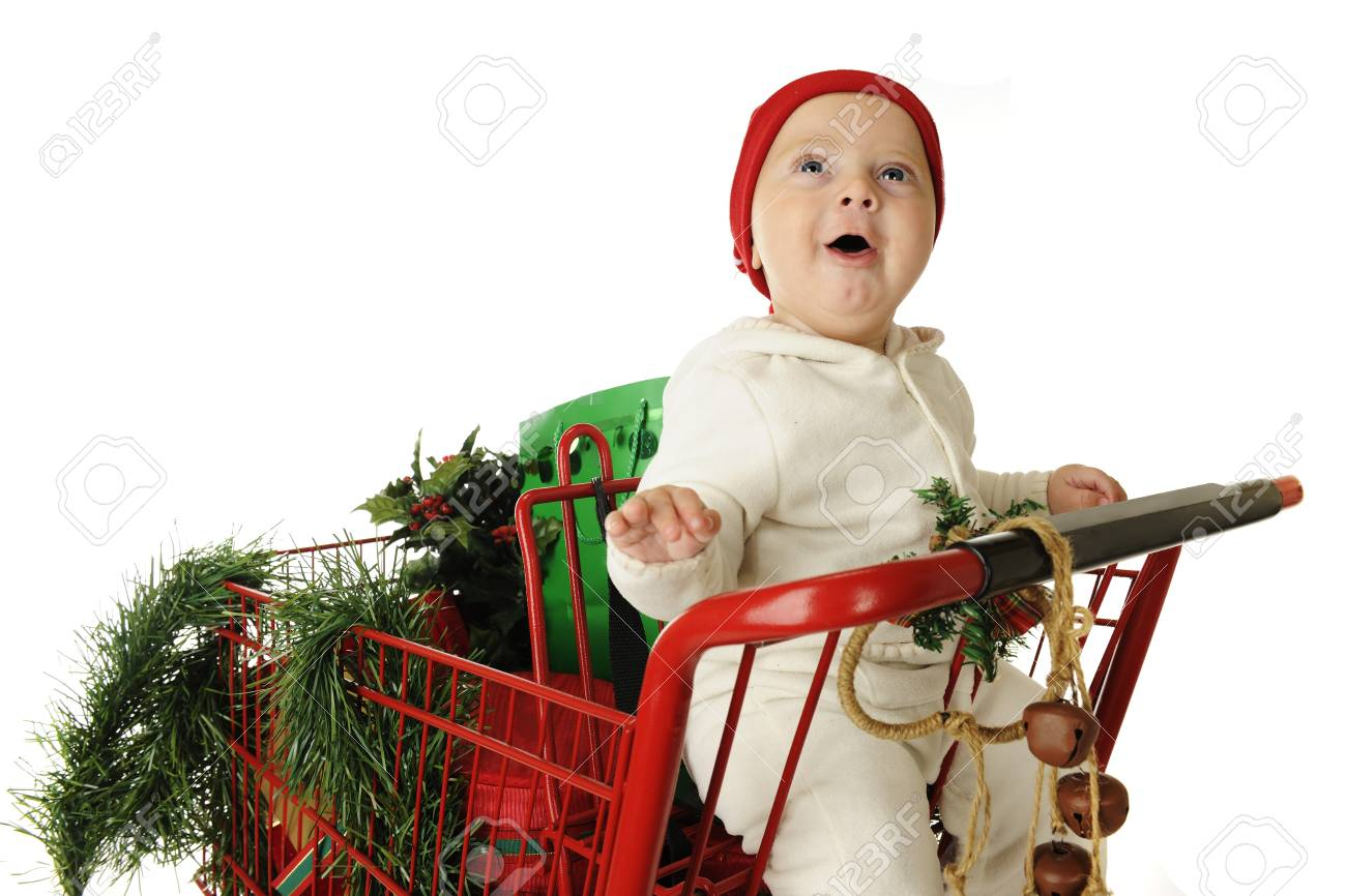 An adorable baby boy delightedly looking up from his seat in a red shopping basket filled with Christmas goodies.  On a white background. Stock Photo - 15416504