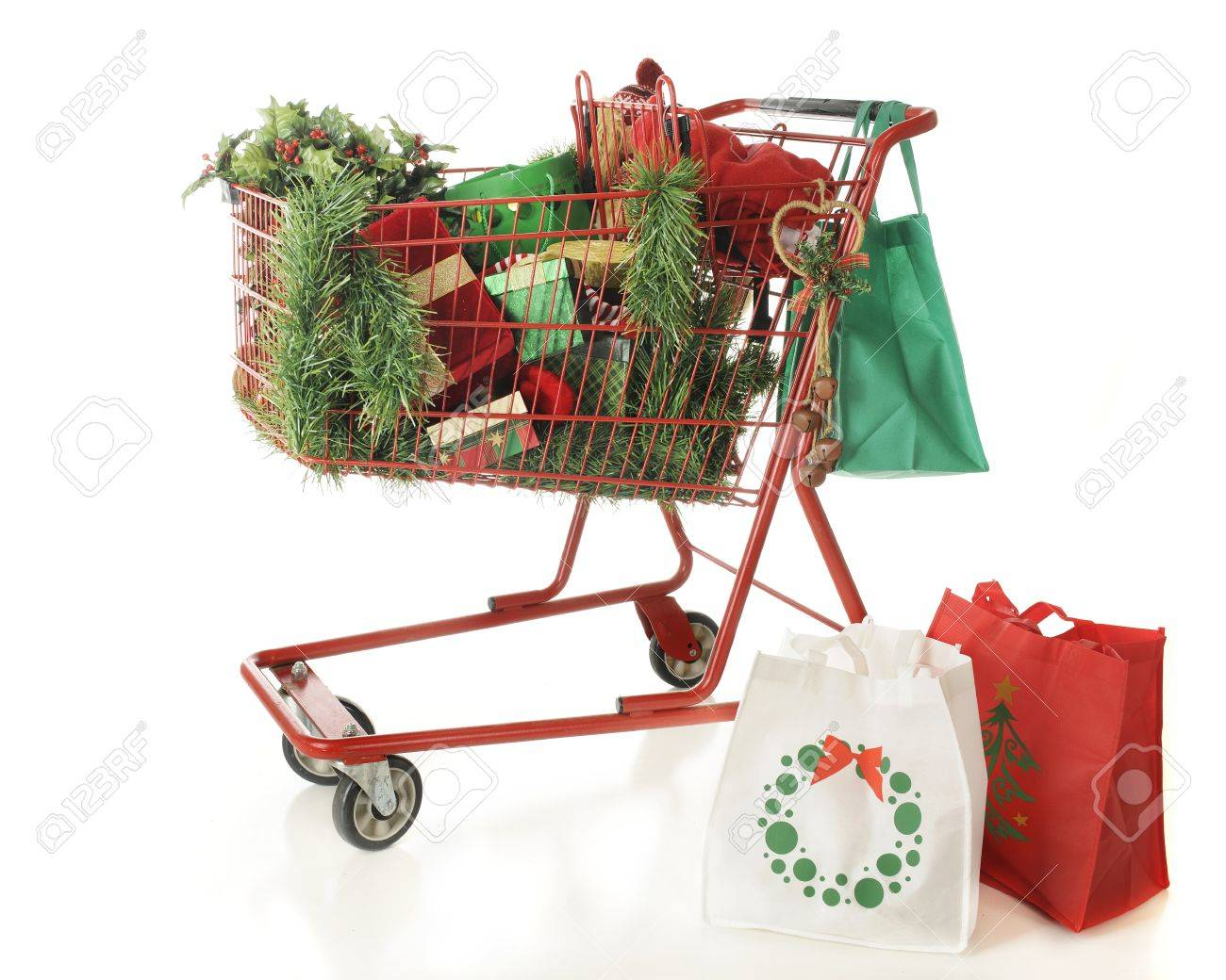 Three reuseable shopping bags and a red shopping basket filled with Christmas shopping goodies   On a white background Stock Photo - 15813107