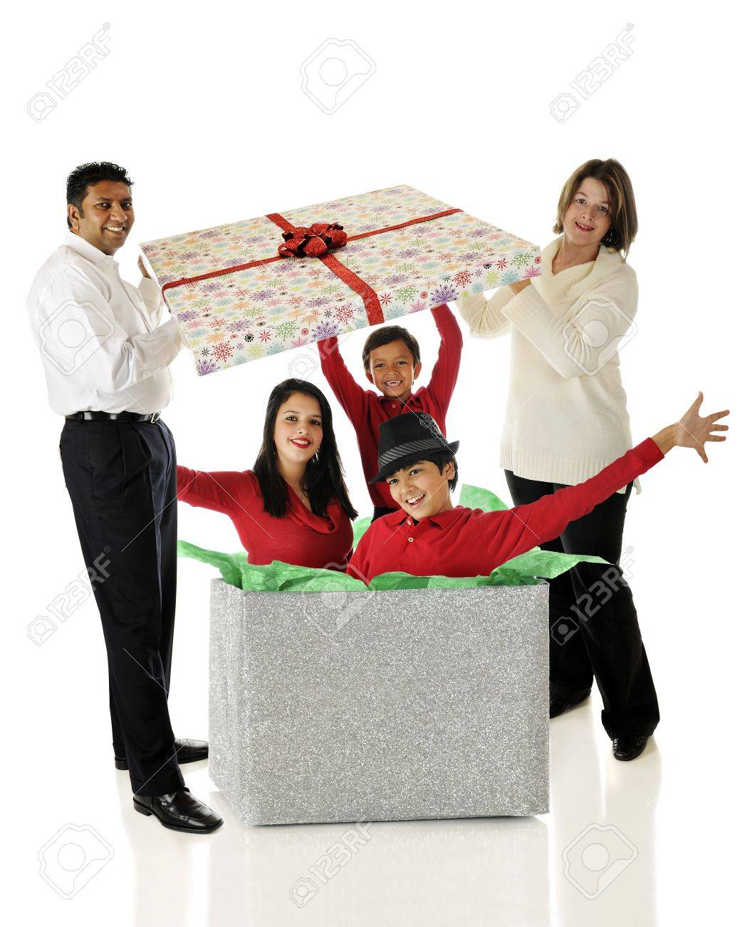 Biracial parents lifting the lid of a giant gift box to happily discover its filled with their three kids.  On a white background. Stock Photo - 15937442