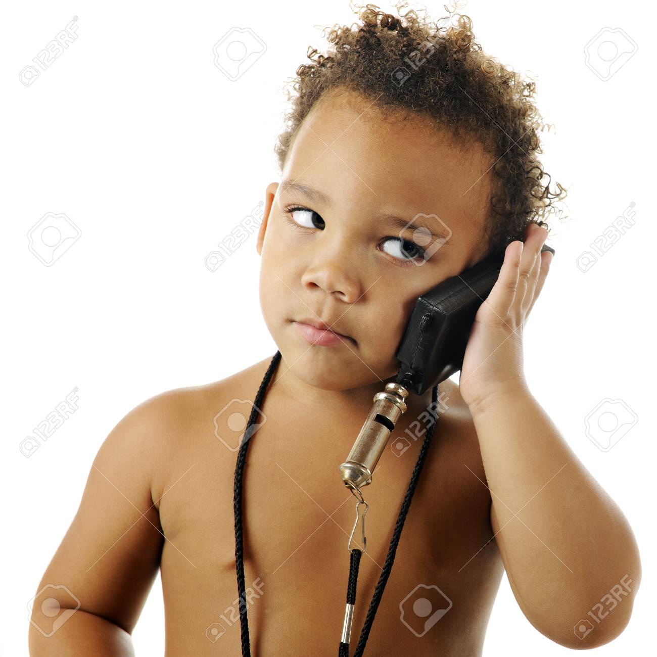 Close-up of an adoreable, bare-chested preschooler listening to a toy (not a phone) that he's pretending to be a phone.  On a white background. Stock Photo - 16366790