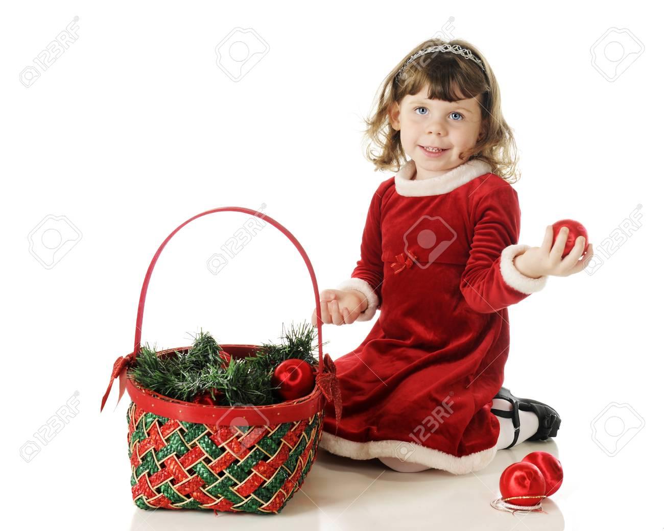 Una Niña Adorable Preescolar Vestidos Para Navidad Felizmente Llenar Una Cesta Roja Y Verde Con Guirnaldas Y Adornos En Un Fondo Blanco
