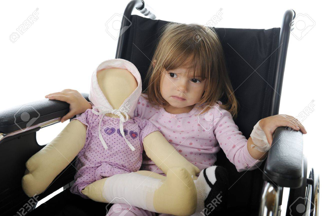 Closeup image of a sad little girl sitting in a wheelchair in her pajamas   She has a doll with bandages like hers Stock Photo - 17036329