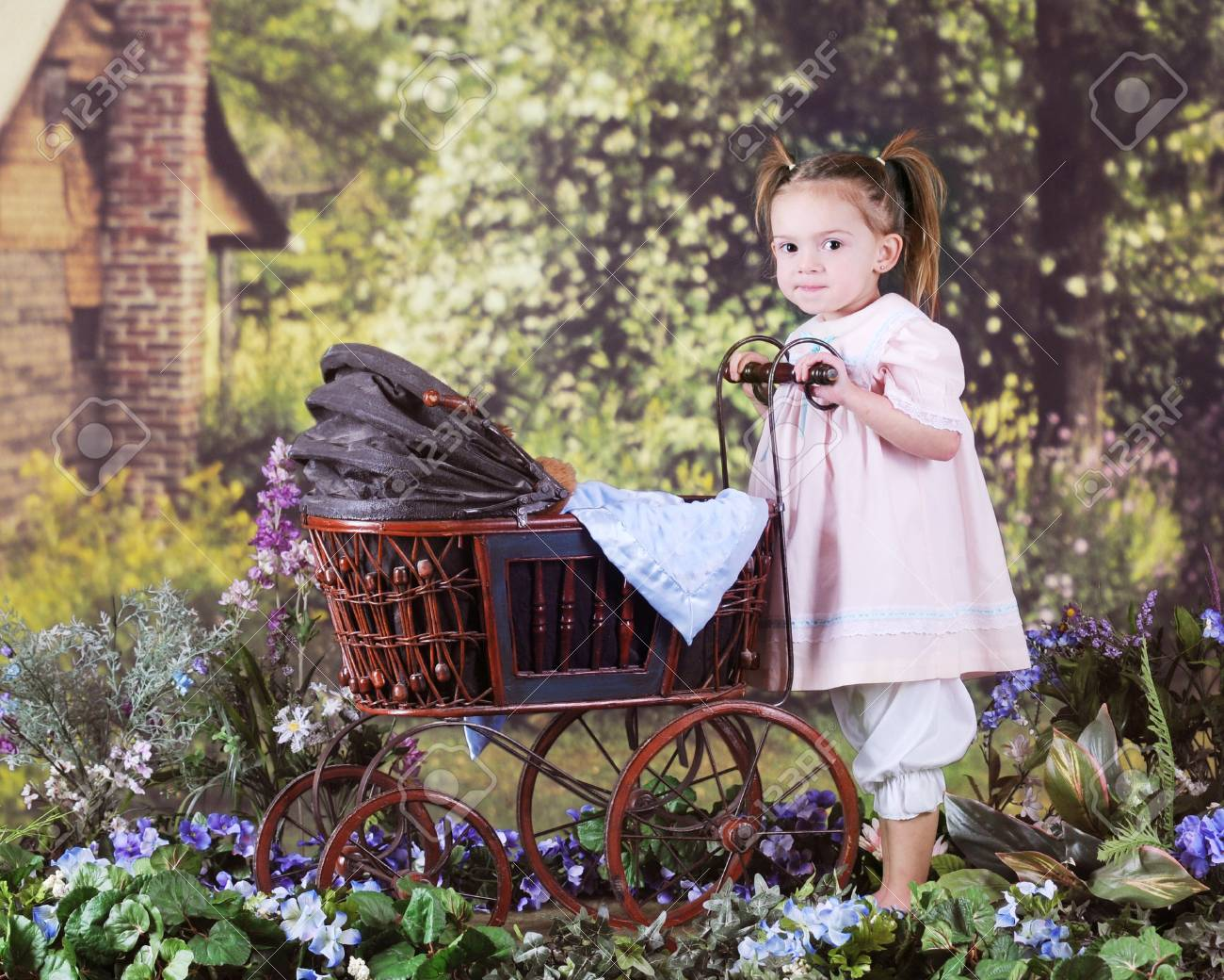 A beautiful preschooler pushing an antique doll buggy in a rustic, rural setting. Stock Photo - 17147962