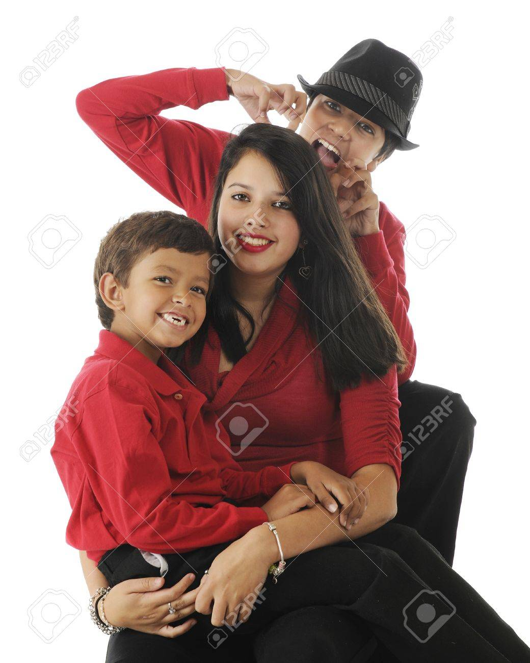 Three biracial siblings (Asian Indian and caucasian) ...a happy preschool boy sitting on the lap of his pretty teen sister with a preteen
